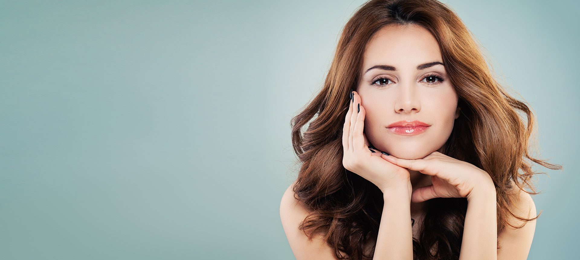 Woman poses while resting chin on hands